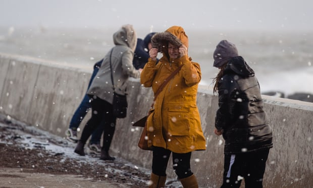 People walk through flying sea foam spray in Porthcawl. Gusts of more than 90mph and heavy rain battered the UK. Photograph: Polly Thomas/Getty Images